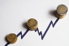 Pièces de monnaie le long des crêtes en hausse d'une ligne de diagramme overview images libres de droits