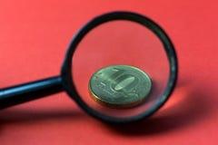Pièces de monnaie par une loupe photographie stock libre de droits