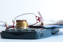 Pièces de monnaie sur la calculatrice, monocle, crayon photographie stock libre de droits