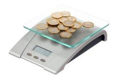 Pièces de monnaie sur les échelles électroniques Image stock