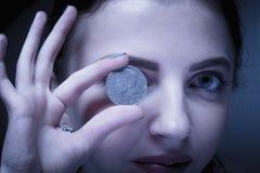 Pièces de monnaie sur les yeux comme symbole du désir d'être riche image libre de droits