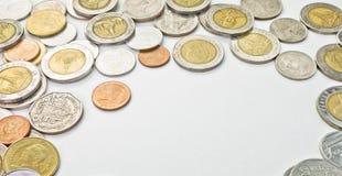 Pièces de monnaie thaïlandaises d'isolement sur l'espace partant blanc au milieu Photo stock