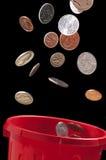 Pièces de monnaie tombant dans la poubelle image stock