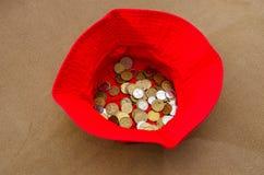 Pièces de monnaie ukrainiennes dans un chapeau rouge photos stock
