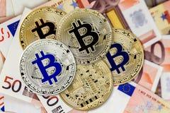 Pièces de monnaie virtuelles de Bitcoin sur des billets de banque d'euros Plan rapproché, macro tir Images libres de droits