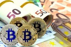 Pièces de monnaie virtuelles de Bitcoin sur des billets de banque d'euros Plan rapproché, macro tir Photos libres de droits