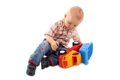 Pièces de petit garçon avec le jouet image stock