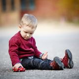 Pièces de petit garçon avec le véhicule de jouet Photos stock