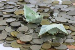 Pièces et billet de devise de la Thaïlande pliés aux bateaux Art d'origami Argent de Thaïlande photographie stock