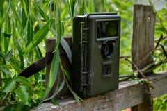 Piège d'appareil-photo avec la lumière infrarouge et détecteur de mouvement attaché avec des courroies sur une barrière en bois Images libres de droits