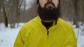 Piédestal tiré du jeune homme avec des yeux bleus et de la barbe dans la forêt neigeuse d'hiver banque de vidéos