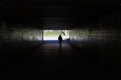 Piéton marchant par le tunnel foncé Photos libres de droits