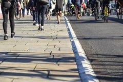 Piétons et cyclistes croisant le pont de Blackfriars à Londres image libre de droits