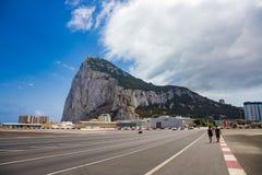 Piétons marchant par la piste de l'aéroport du Gibraltar Photos stock