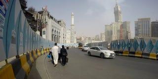 Piétons se dirigeant à la mosquée grande dans Mecque et Mecca Royal Clock Tower Hotel images stock