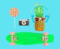 Piña con el monopatín de la cámara del vintage del caramelo de la piruleta de las gafas de sol de los auriculares Imagen de archivo libre de regalías