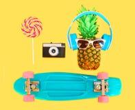 Piña con el monopatín de la cámara del vintage del caramelo de la piruleta de las gafas de sol de los auriculares sobre amarillo  Fotografía de archivo