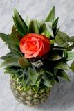 Piña con la rosa del rojo en una tabla de mármol Fotografía de archivo libre de regalías