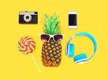 Piña con smartphone de la cámara del vintage de la piruleta de los auriculares de las gafas de sol sobre amarillo colorido Foto de archivo libre de regalías