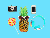 Piña con smartphone de la cámara del vintage de la piruleta de los auriculares de las gafas de sol sobre azul colorido Fotos de archivo libres de regalías