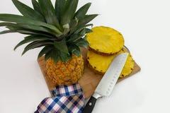 Piña cortada con las rebanadas y el cuchillo imagenes de archivo