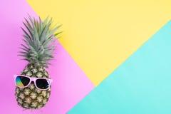 Piña de los accesorios de la playa con las gafas de sol rosadas en el fondo del rosa, verde y amarillo para el concepto de las va fotos de archivo