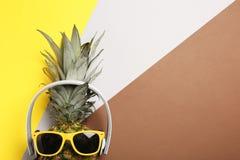 Piña divertida con los auriculares y las gafas de sol en el fondo del color, visión superior fotos de archivo