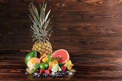 Piña, pomelo vivo, peras, fresas, hojas de la menta, arándanos, cal e hielo en un fondo marrón de madera Imagen de archivo