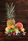 Piña, pomelo vivo, peras, fresas, hojas de la menta, arándanos, cal e hielo en un fondo marrón de madera Fotos de archivo libres de regalías