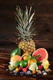 Piña, pomelo vivo, peras, fresas, hojas de la menta, arándanos, cal e hielo en un fondo marrón de madera fotos de archivo