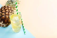 Piña y jugo con hielo en un vidrio, en un fondo amarillo azul Humor del verano, espacio de la copia fotos de archivo