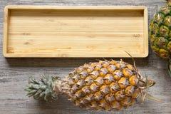Piña y placa de madera Foto de archivo libre de regalías