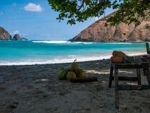 Piñas en un taburete en una playa con agua azul Fotografía de archivo