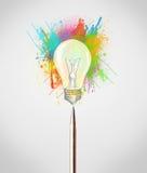 Pióra zakończenie z barwionymi farb pluśnięciami, lightbulb i Obraz Stock