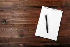 Pióro i notatnik na czerwonym drewno stole Odgórny widok Obrazy Royalty Free
