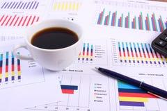 Pióro, kalkulator i filiżanka kawy na pieniężnym wykresie, biznesowy pojęcie obrazy royalty free