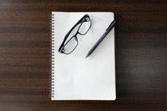 Pióro notatnik na drewno stole i szkła Fotografia Stock