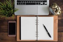 Pióro, smartphone, zegar, notatnik, laptop na drewnianym stole obrazy stock