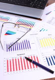 Pióro, szkła i laptop na pieniężnym wykresie, biznesowy pojęcie obrazy stock