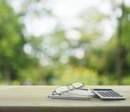 Pióro, szkła, notatnik i kalkulator na drewnianym stole nad zielenią, Zdjęcia Royalty Free