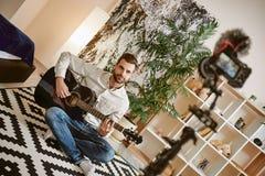 Più abbonati Blogger maschio barbuto di musica che si siede sul pavimento e che tiene la chitarra, mentre registrando nuovo video fotografia stock libera da diritti