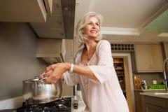 Più vecchia acqua bollente sorridente della donna sulla cima della stufa di cucina Fotografia Stock