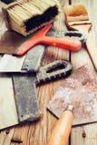 Più vecchie spatole e spazzole su un fondo di legno tinto Immagini Stock Libere da Diritti
