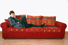 Più vecchio, il fare chiacchiere maturo della donna sul telefono cellulare sul sofà Fotografie Stock
