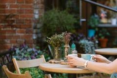 pić herbatę kobieta trzyma filiżankę napój podczas gdy siedzący przy caf obraz royalty free