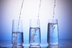 Pić szkła z odbiciem w kroplach Wodny dolewanie obraz stock