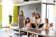 Pięć żeńskich kolegów spotyka uśmiecha się kamera przy pracą obraz stock