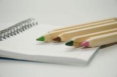 Pięć barwili drewnianych ołówki na tle pusty prześcieradło notepad obrazy stock