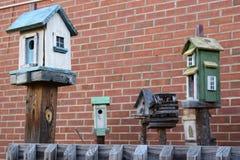 Pięć birdhouses z ściana z cegieł tłem Fotografia Royalty Free