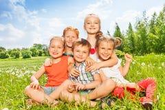 Pięć cudownych dzieciaków siedzi wpólnie na łące Fotografia Royalty Free